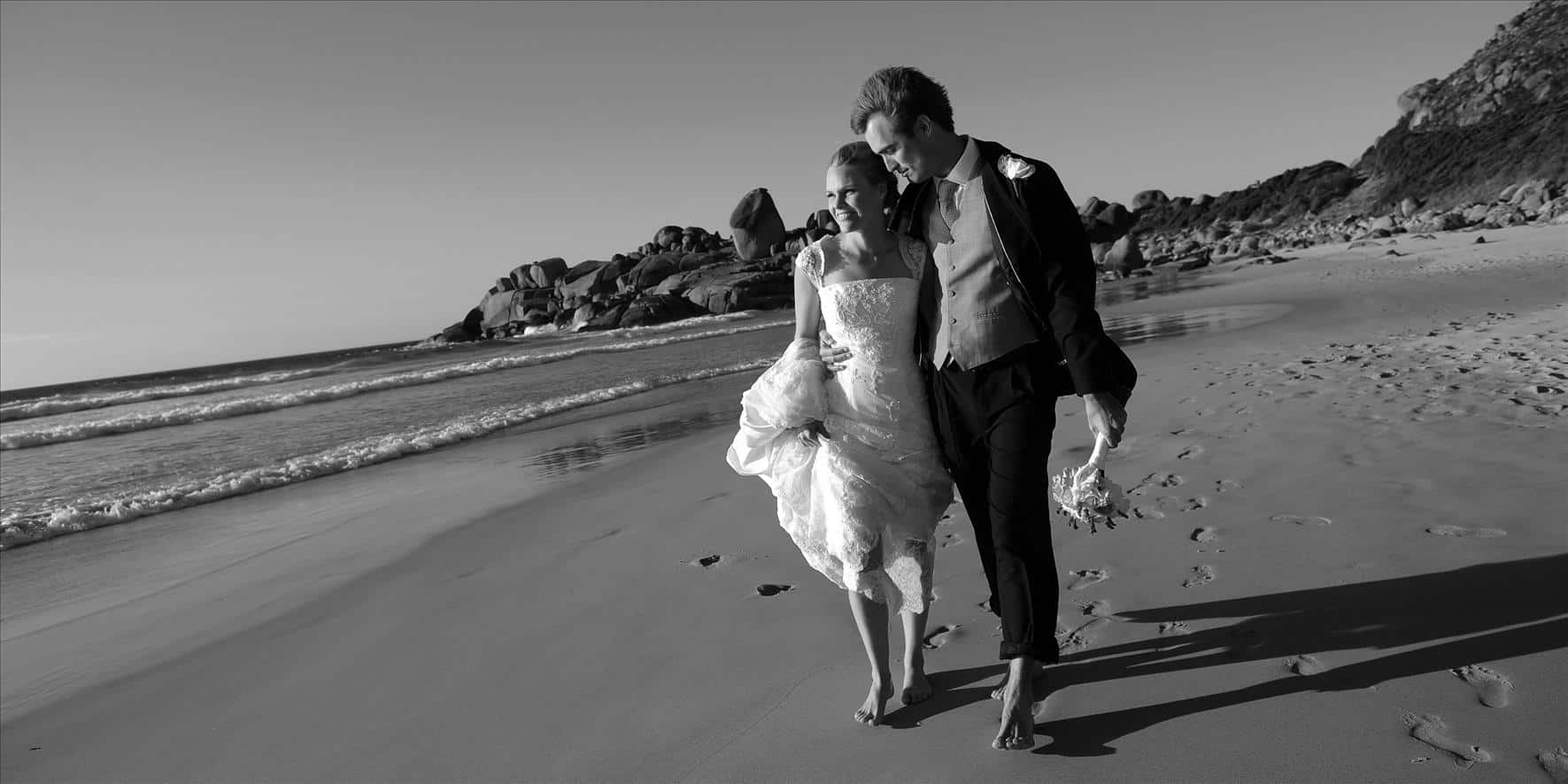 married couple walking sea shore greyscale